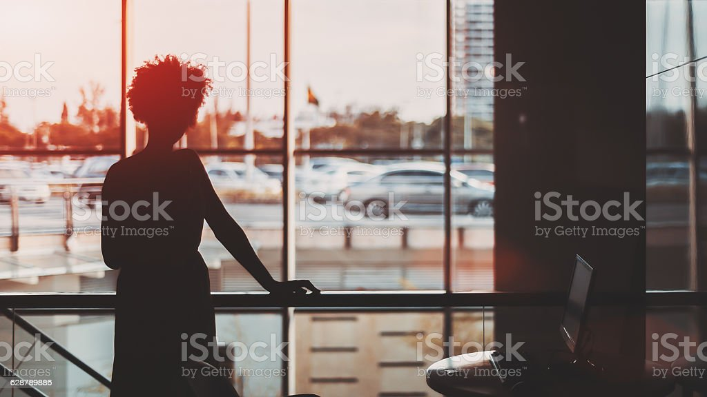 Silhouette of black curly girl in front of window stock photo