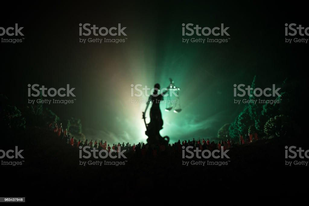 Silhouette of blurred giant lady justice statue with sword and scale standing behind crowd at night with foggy fire background. - Zbiór zdjęć royalty-free (Biznes)