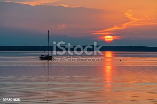 Silhouette of boat on lake Steinhuder Meer at sunset, Lower Saxony, Germany.