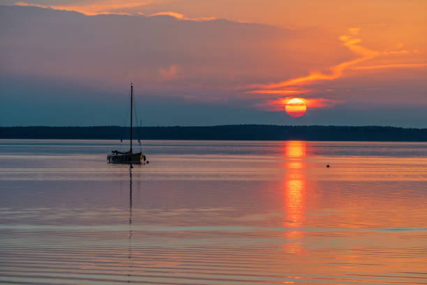 Silhouette of boat on lake Steinhuder Meer at sunset, Lower Saxony, Germany stock photo