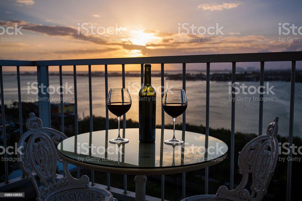 Silhouette de bouteille et verre de vin rouge au coucher du soleil photo libre de droits
