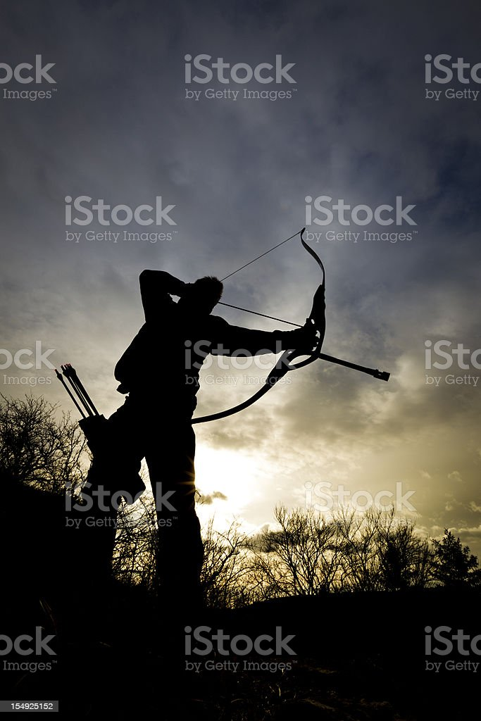 Silhouette of bow hunter at sundown stock photo