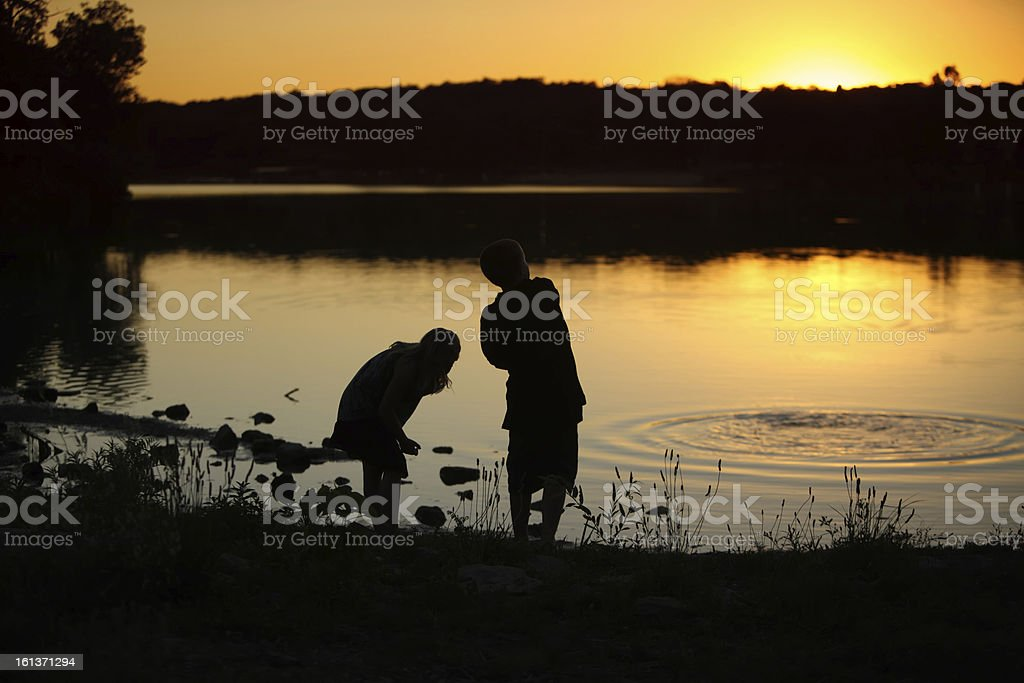 Silhouette of Boy and Girl Skipping Rocks at Sunset stock photo