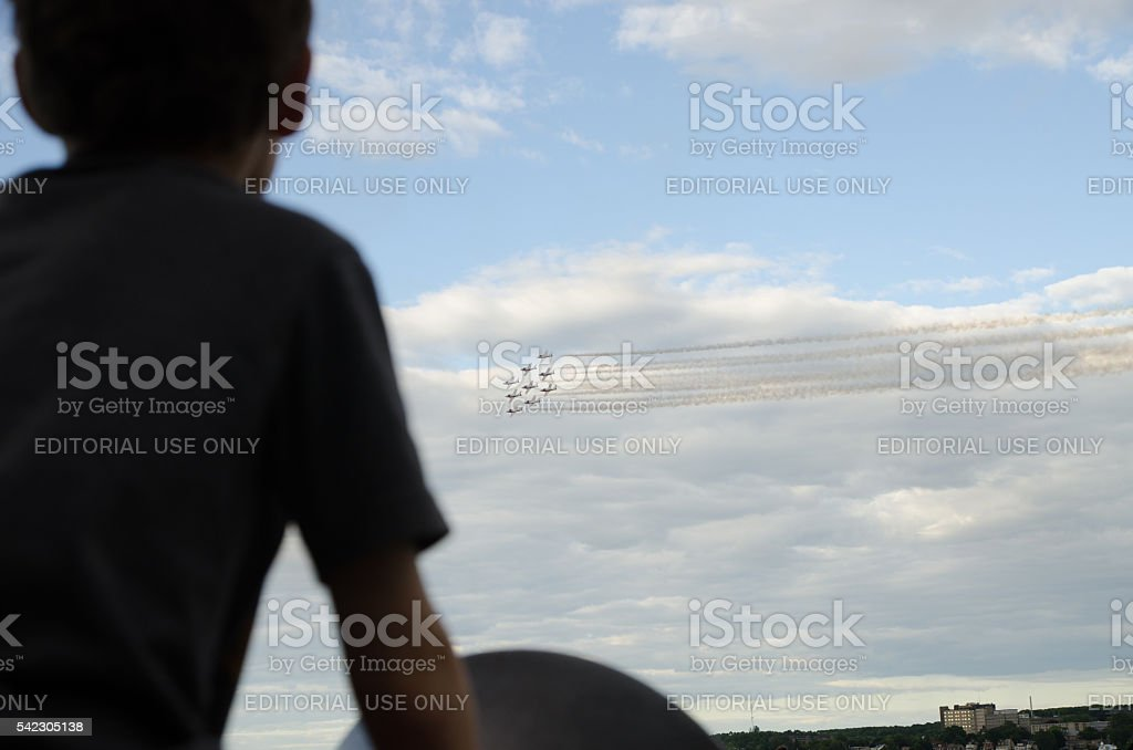 Silhouette of boy looking at fighter aircraft during airshow stock photo