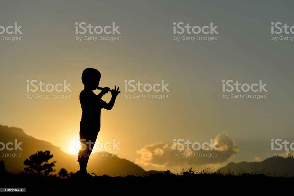 silhouette of boy playing the flute stock photo