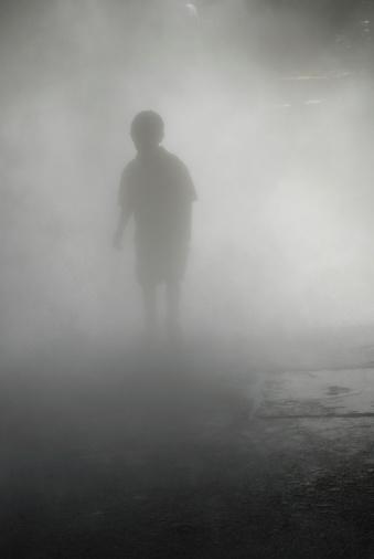 A boy walking through the mist