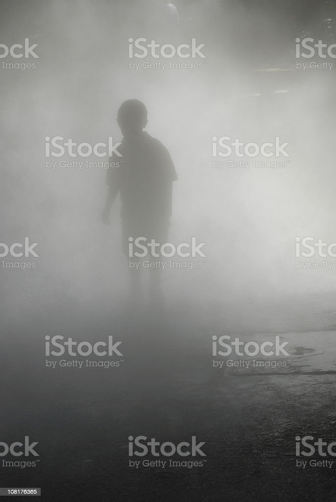 Silhouette of Boy Walking Through Heavy Fog stock photo