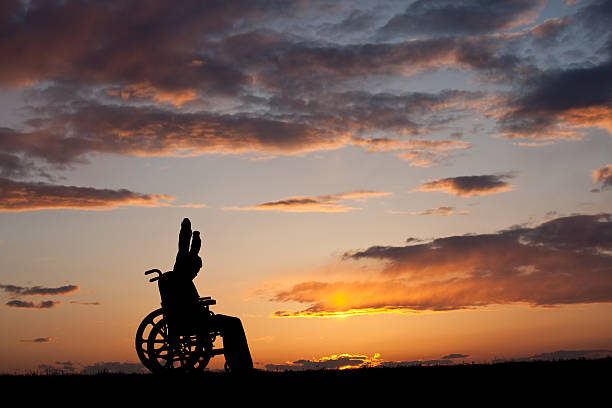 Silhouette of Boy With Physical Handicap in a Wheelchair stock photo