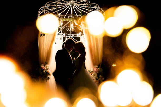 Silhouette of bride and groom on night ceremony. Wedding arch with lights stock photo