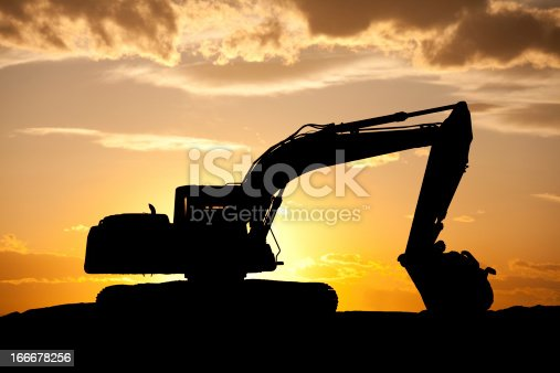 A silhouette of a bulldozer on a construction site. This large earth mover, or bulldozer, is situated on a residential development site near Calgary, Alberta. Heavy equipment operators earn a very comfortable living, however, there is plenty to learn in this trade as this industrial equipment requires plenty of know-how. Nobody is in this image, taken in mid-summer near Cranston, Calgary.