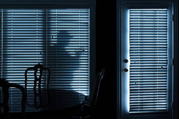 Silhouette of Burglar Sneeking Up To Backdoor At Night stock photo