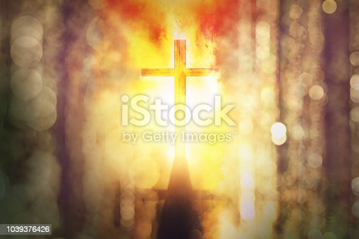 istock silhouette of burning cross with rays of sunlight background 1039376426