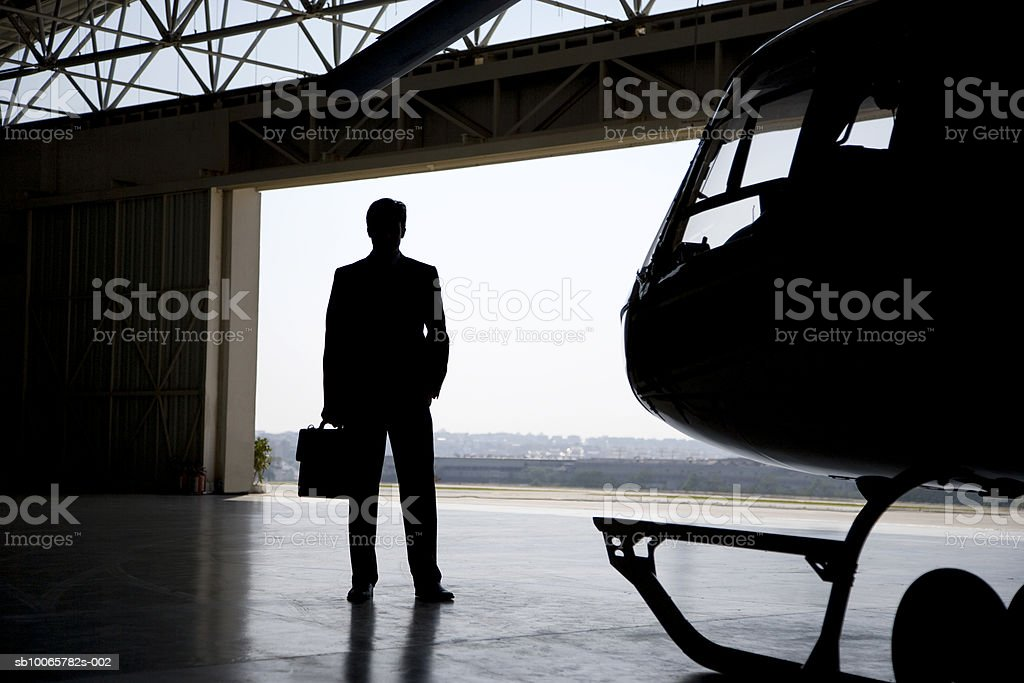 Silhouette of business man in front of helicopter, hangar foto stock royalty-free