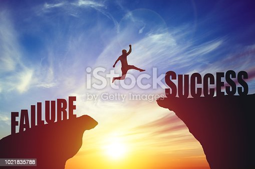 Silhouette of business man jump to success text over a beautiful high view mountain background