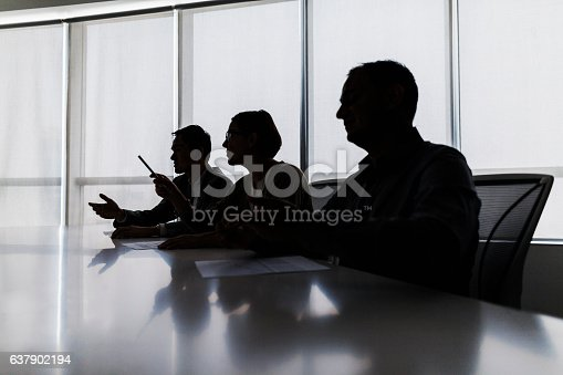 istock Silhouette of business people negotiating at meeting table 637902194