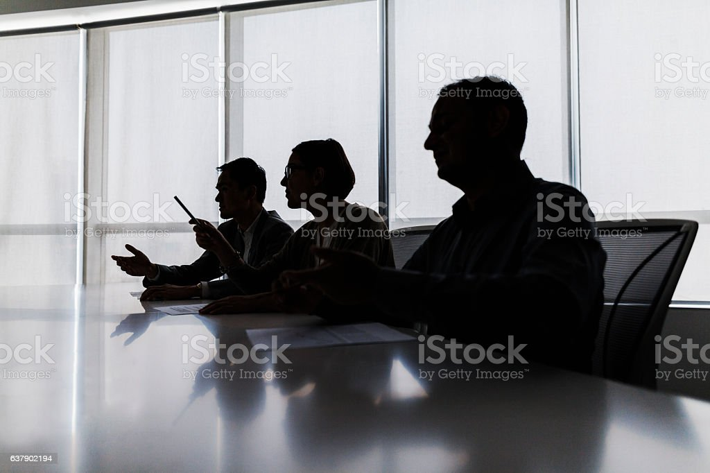 Silhouette of business people negotiating at meeting table - foto de acervo