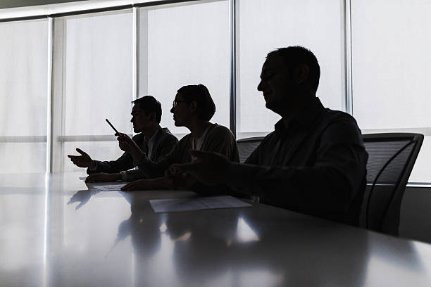 Silhouette of business people negotiating at meeting table Silhouette of business people negotiating at meeting table governing board stock pictures, royalty-free photos & images