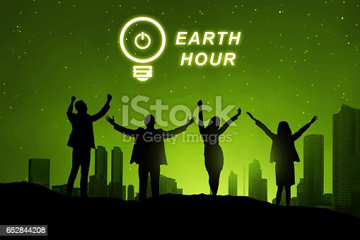 Silhouette of business people with Earth hour message over cityscape background