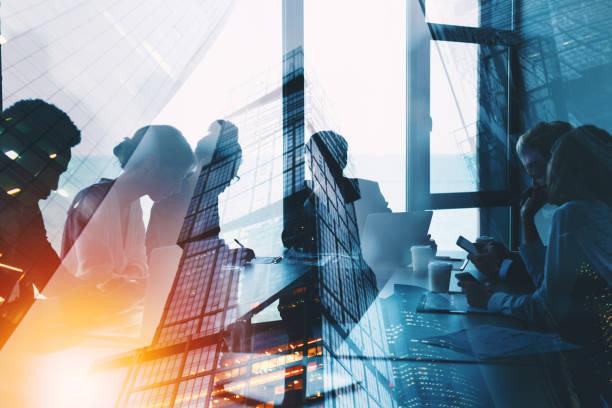 商務人士的剪影在辦公室裡一起工作。團隊合作和夥伴關係的概念。具有光效的雙重曝光 - 商務 個照片及圖片檔
