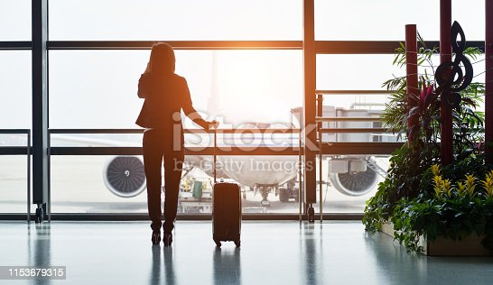 istock Silhouette of business traveler makes a call while waiting for her flight 1153679315