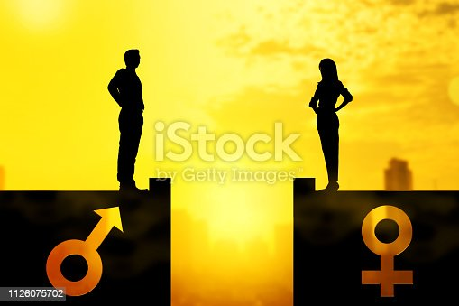 istock Silhouette of businessman and businesswoman standing on the rooftop with same height 1126075702