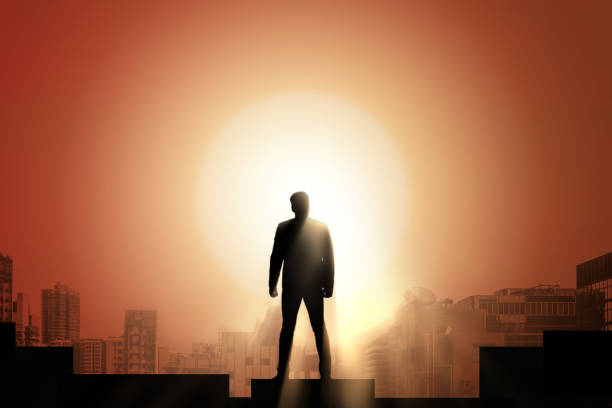 Silhouette of businessman on mountain with sunset sky background. Business success and leadership concept. stock photo