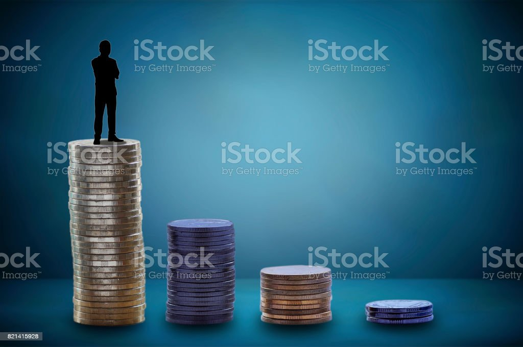 silhouette of businessman stranding on stacked of coins and money  growing up and success in business, concept as improve, profit and capital banking stock photo
