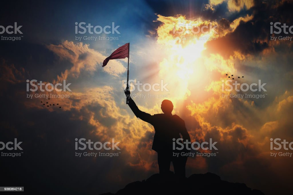 silhouette of businessman with flag on top of mountain against sun light stock photo