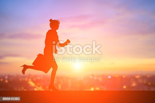 silhouette of business woman running with sunset