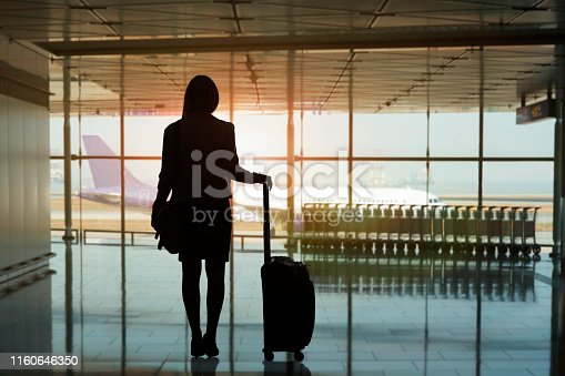 istock Silhouette of businesswoman waiting for flight with suitcase at Hong Kong International Airport 1160646350