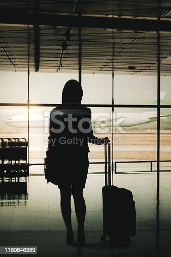 istock Silhouette of businesswoman waiting for flight with suitcase at Hong Kong International Airport 1160646389