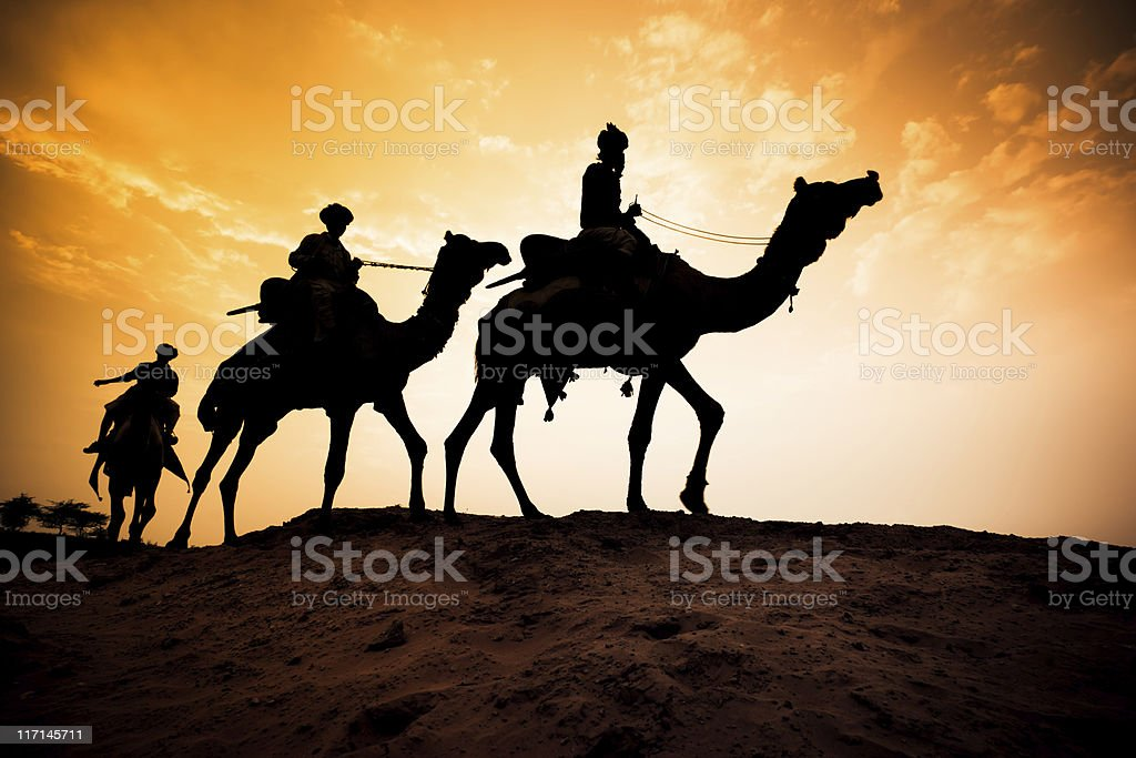Silhouette of Camel Caravan at Desert Sunset stock photo