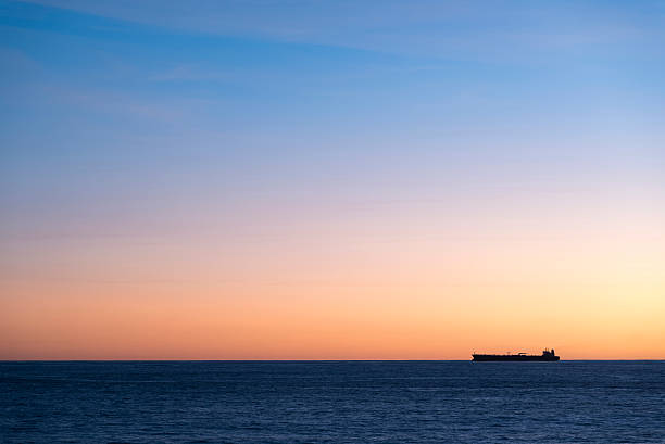 silhouette  of cargo ship on the horizon - mahroch stock pictures, royalty-free photos & images