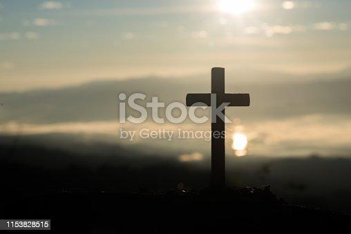 istock Silhouette of catholic cross and sunrise 1153828515