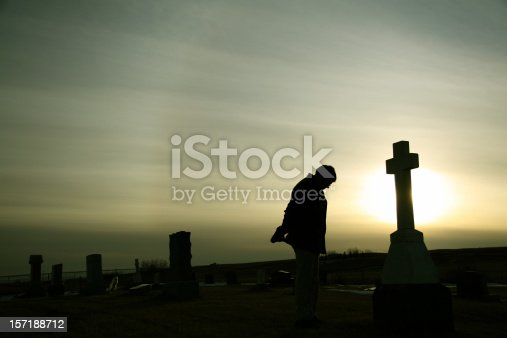 A man remembers a loved one beside a tombstone at a graveyard. Additional themes include death, loss, funeral, remembering, tribute, memorial, memorial day, veteran's day, sadness, heaven, cemetery, and grief. Unrecognizable man in 30s.
