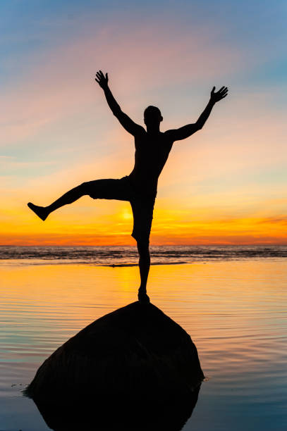 Silhouette of cheerful balancing on stone in water funny man. stock photo