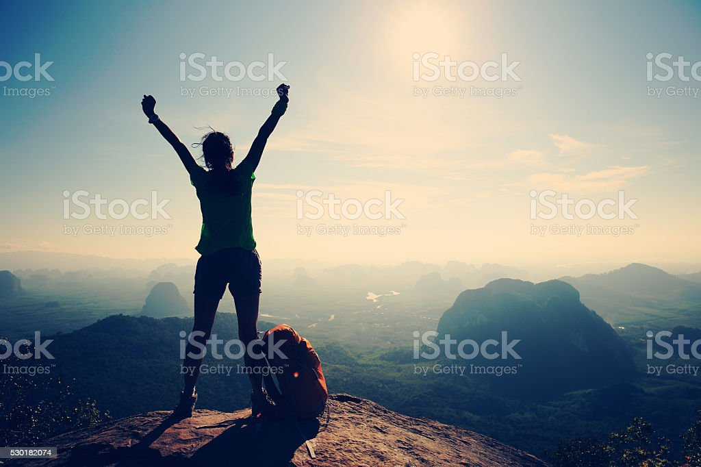 silhouette of cheering woman hiker open arms at mountain peak stok fotoğrafı
