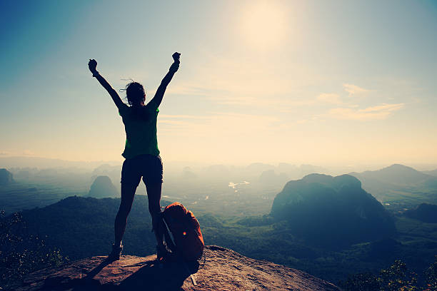 silhouette of cheering woman hiker open arms at mountain peak - bold stock photos and pictures