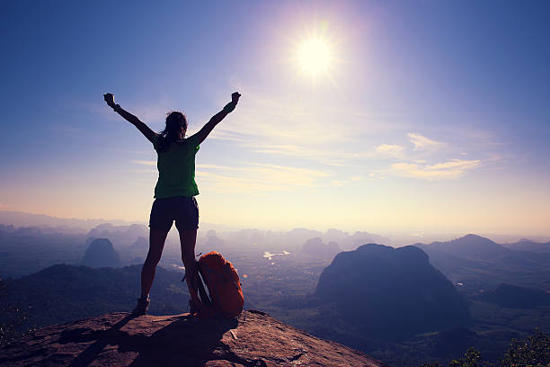silhouette of cheering woman hiker open arms at mountain peak - dedication stock photos and pictures