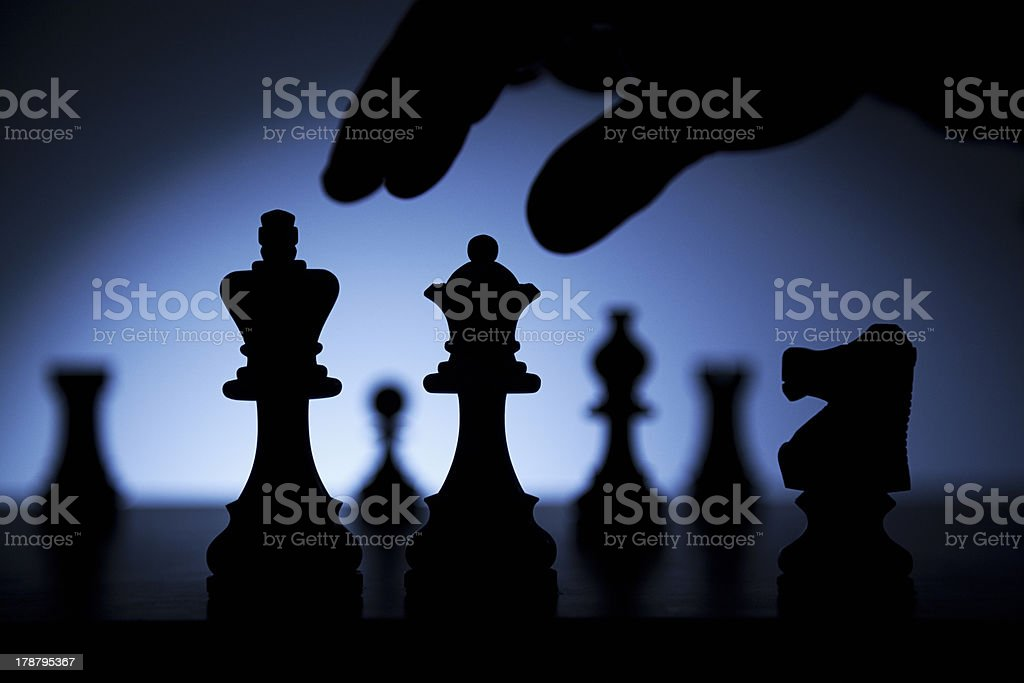 Silhouette of chess set and hand ready to play stock photo