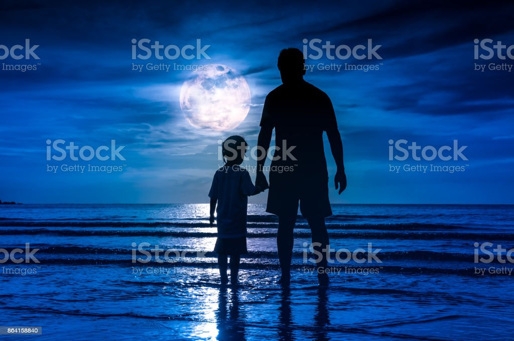 Silhouette of child holding hands her father, standing in the sea. royalty-free stock photo