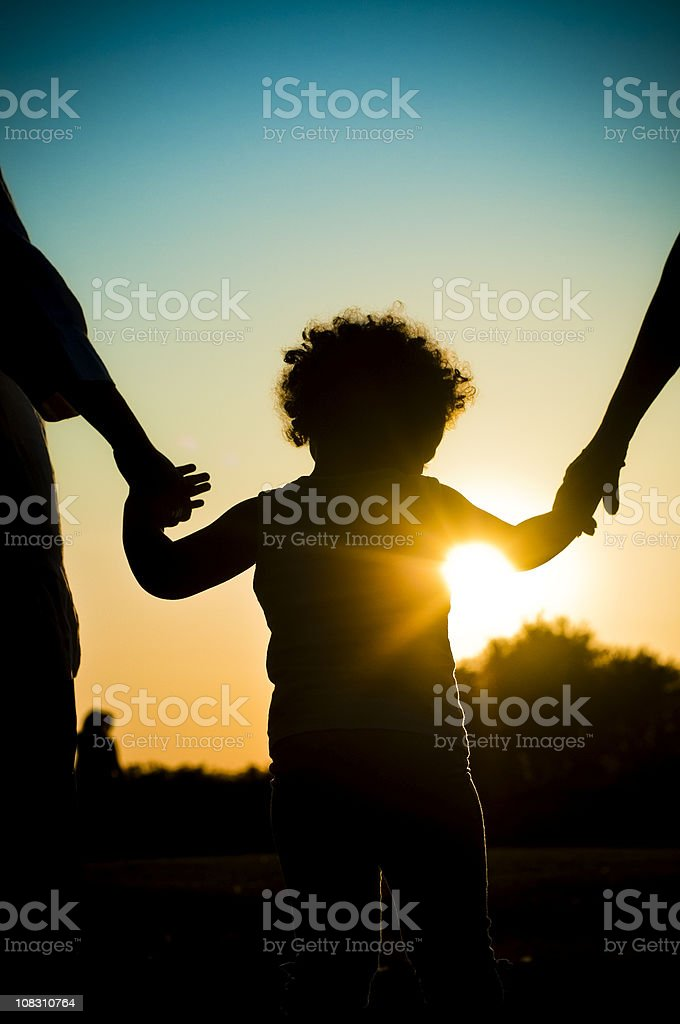 Silhouette of Child Holding Hands stock photo