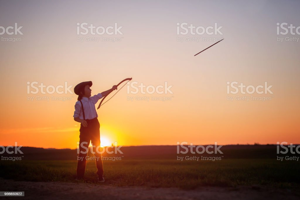 Silhouette of child playing with bow and arrows, archery shoots a bow at the target stock photo