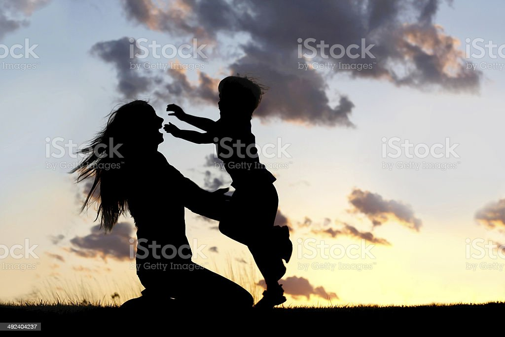 Silhouette of Child Running to Hug Mother at Sunset stock photo