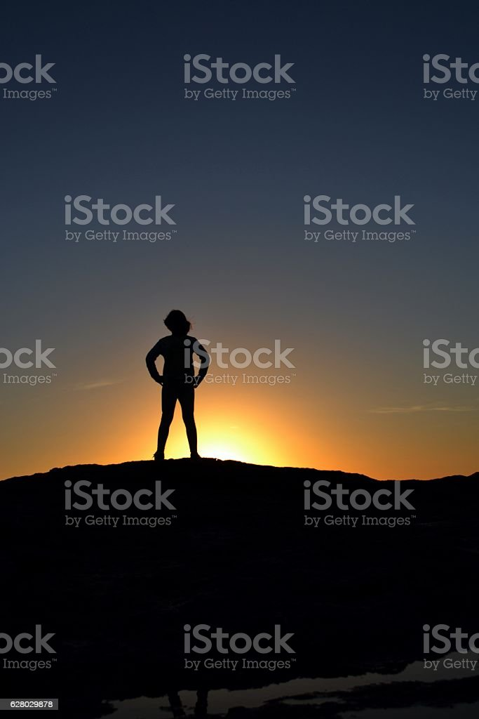 silhouette of child standing on a rock facing the sunset stock photo