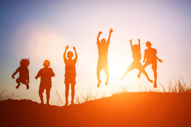 Silhouette of children jump gladness happy time stock photo