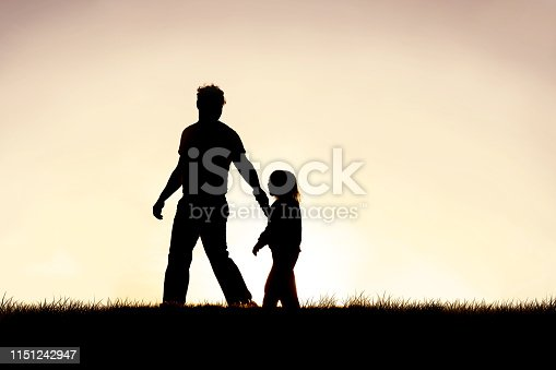 The silhouette of a young Christian father is guiding his young child by the hand as they walk outside at sunset.