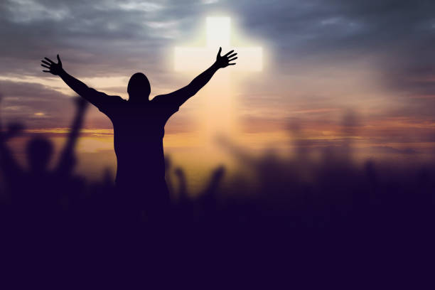 silhouette of christian prayers raising hand while praying to the jesus - praise and worship stock photos and pictures
