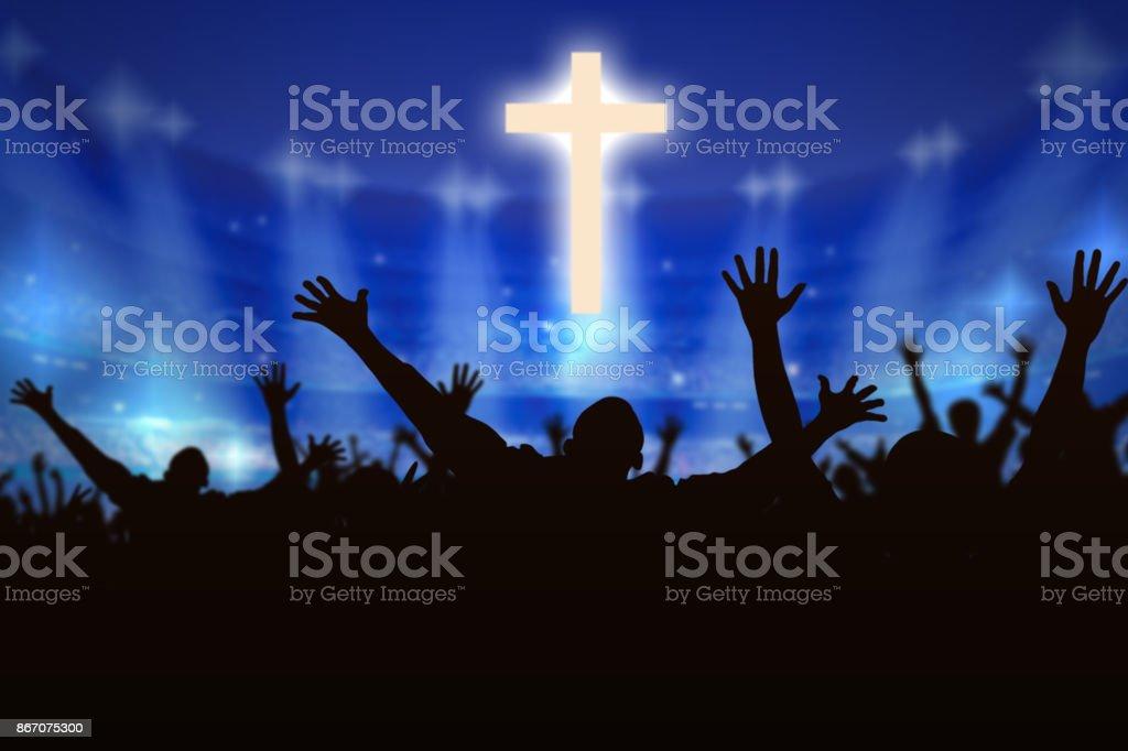 Silhouette of Christian prayers raising hand while praying to the Jesus stock photo