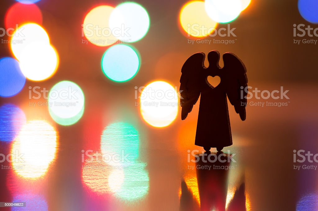 Silhouette of Christmas angel with hole in form of heart stock photo